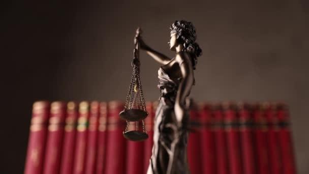 nemzetközi bronz jelképe jog által képviselt bekötött szemmel istennő kezében egyensúlyt jelképező két széles jogforrás, pártatlanság és a hatalom, forog lassan előtt piros könyvek barna háttér