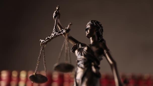 igazságszolgáltatás szobor által képviselt bekötött szemmel hölgy kezében egyensúly és a kard jelképezi a hatalom és pártatlanság, forgó egyetemi szobában a háttérben készült könyvek