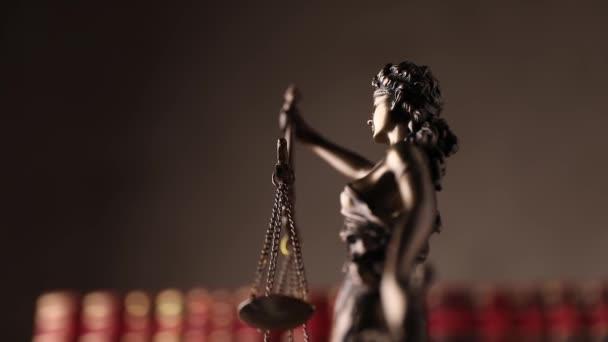 lefelé nézet igazságszolgáltatás szobor által képviselt bekötött szemmel hölgy kezében egyensúly és a kard jelképezi hatalom és pártatlanság, forgó előtt piros könyvek barna háttér