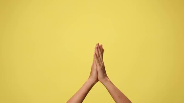 két kéz tapsol, rámutatva a kamerára, egymásra mutogatva és megünnepelve a sikert sárga alapon