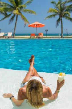Beautiful woman at the swimming  pool at the tropical resort