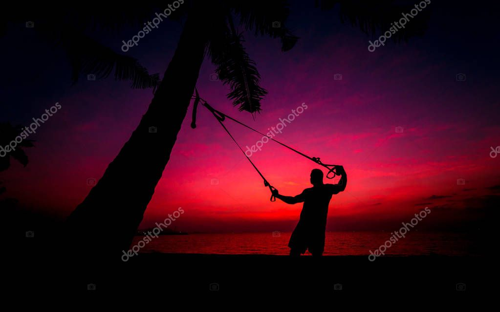 The athlete performs exercises on the beach with fitness straps which are fixed on the palm tree. Sunset. Background