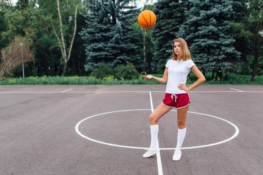 Beautiful young girl dressed in white t-shirt, shorts and sneakers, plays with a ball on a basketball court.