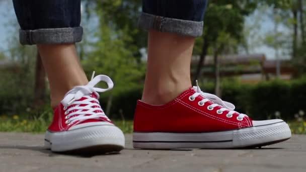 Frauenfüße in roten Turnschuhen unterwegs in der Stadt