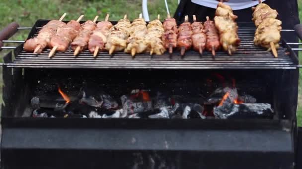 Šéfkuchař připravuje barbecue. Chutný chutné smažené kousky masa na špízu se praží na velký venkovní gril