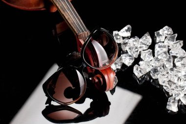 Sunglasses, violin, pieces of ice on a glass background