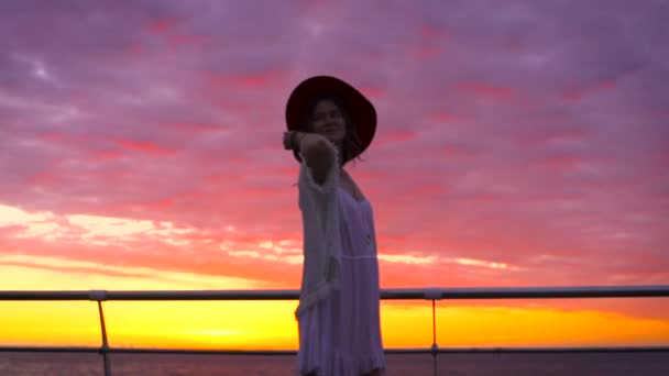 young attractive woman wearing white dress and hat posing on sea background at amazing sunset