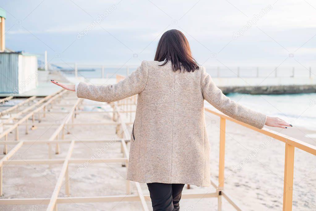 outdoor portrait of stylish brunette woman wearing grey coat posing on sea background, rear view
