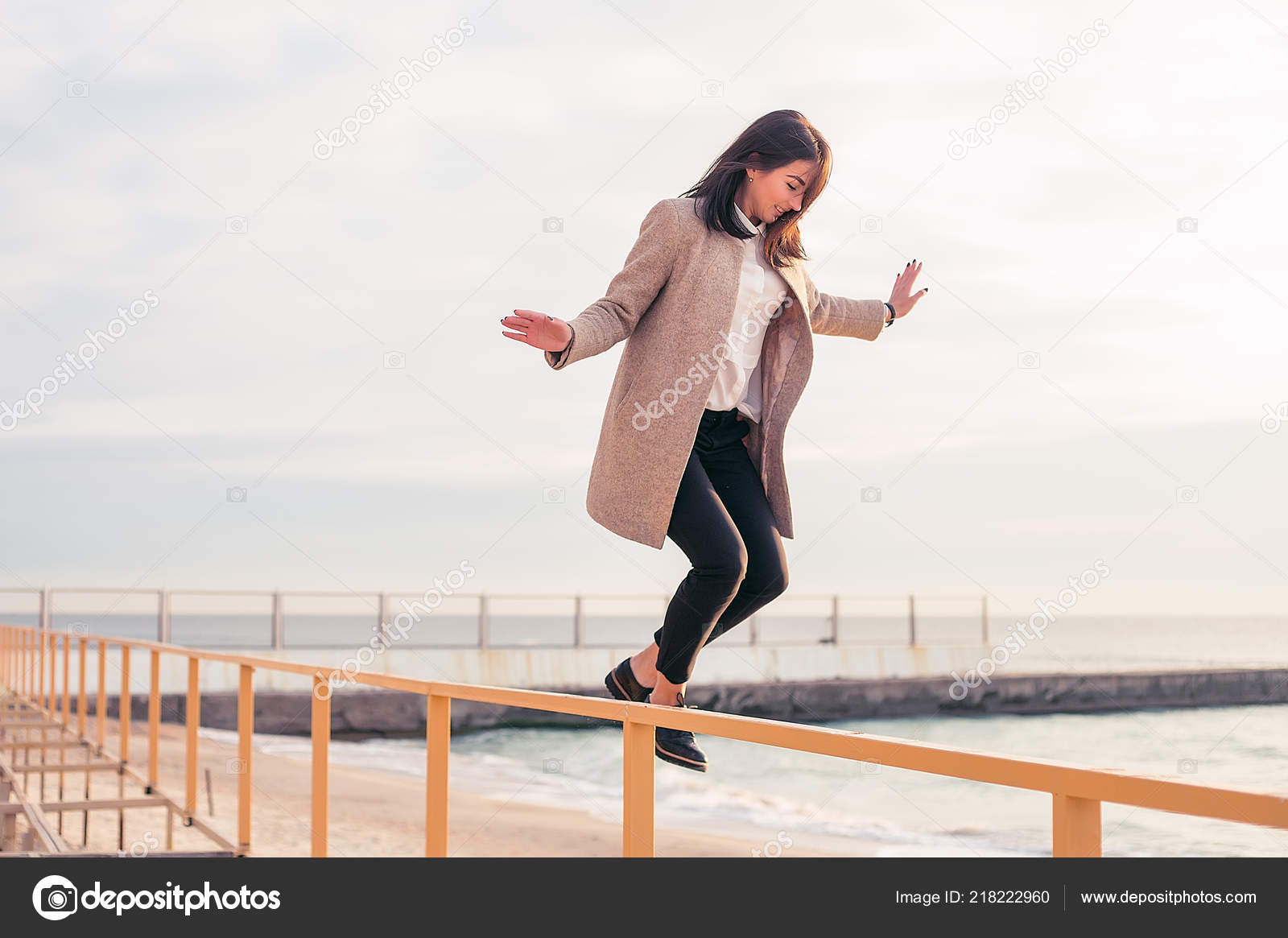 Elegáns barna nő visel a szürke kabátot ugrálva korlát a tenger háttér 002d075a6a