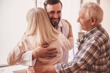 Handsome doctor is meeting an old couple of patients, hugging woman and smiling