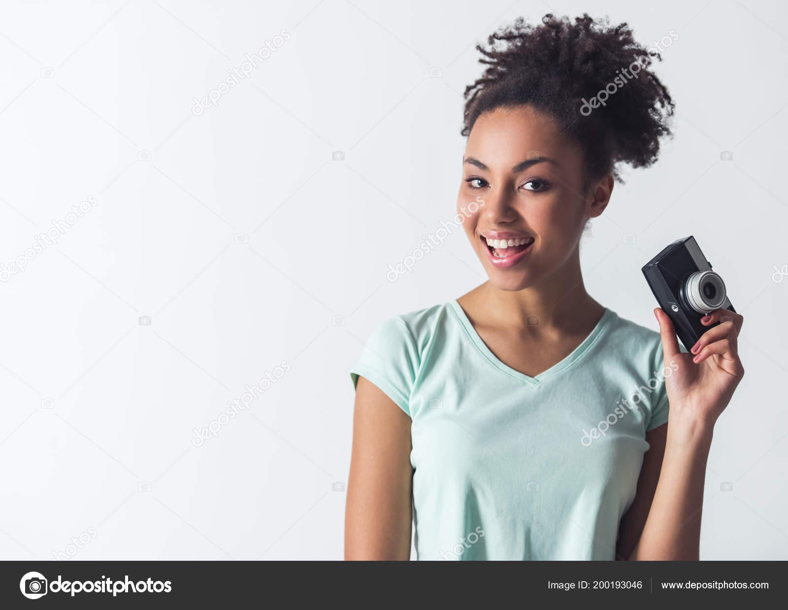 c311ca87fb01 Ragazza Afro-American allegra in abbigliamento casual è in possesso di una  macchina fotografica e sorridente
