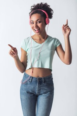 Stylish Afro-American girl in casual clothes and headphones is listening to music, looking at camera and smiling, isolated on white