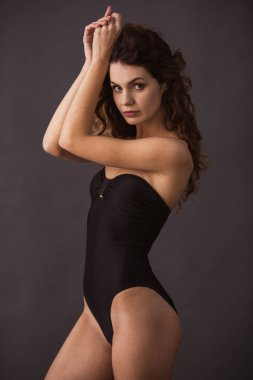 Portrait of a young beautiful sexy girl in a swimsuit on a black background