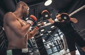 Photo Afro American boxer in gloves is training with a coach in the boxing ring
