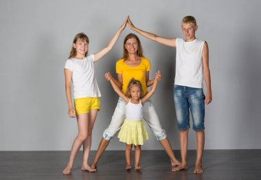 Family is standing on a gray background studio