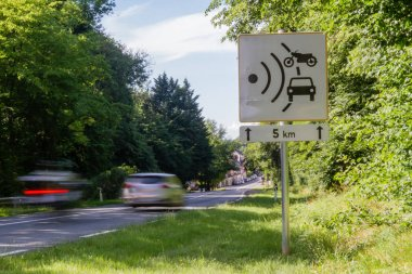 Speed limit speed camera sign with cars driving too fast