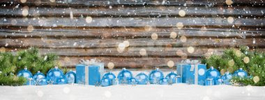 Blue christmas gifts and baubles lined up on wooden background 3D rendering