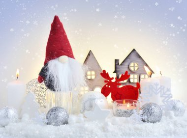 Christmas composition with the gnome, elk, candles, toy houses and festive decorations. Christmas or New Year greeting card.