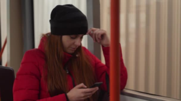 Young caucasian woman talking on mobile phone during evening bus ride. Defocused urban traffic in the bus window slow motion 4K shot