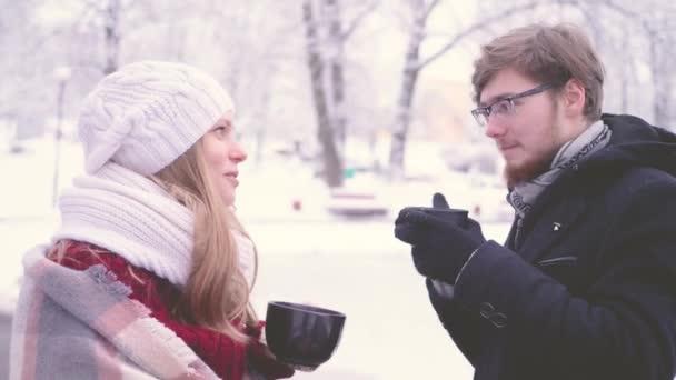 Mladá žena tisícileté a vousatý muž s brýlemi, s úsměvem a prochlastali horké kakao z kelímků v rukou v zimě parku. 4 k slow-motion záběry.