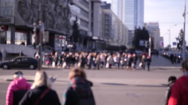 blurred unrecognizable crowd of people crossing the road at a traffic light in the morning sunlight in the business district of a lively city in slow motion 4K video
