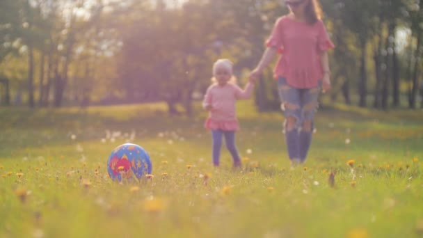 young woman and her little daughter are walking in bright sunlight in the city park on sunset and mother holding babys hand and then the girl runs up to the ball and kicks it. Happy parenting concept