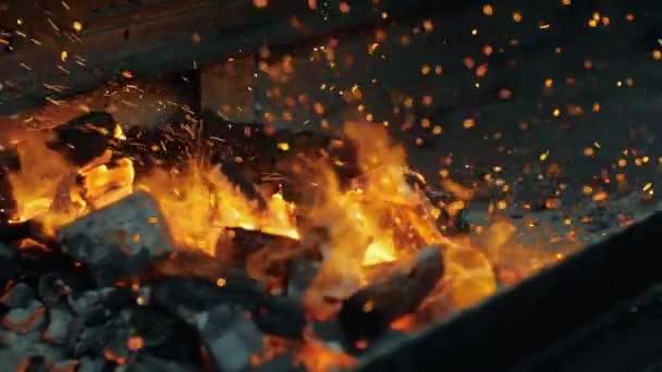 Střepy ohnivé jiskry, pohybující se na černém pozadí, přicházející z jasně teplého ohně.