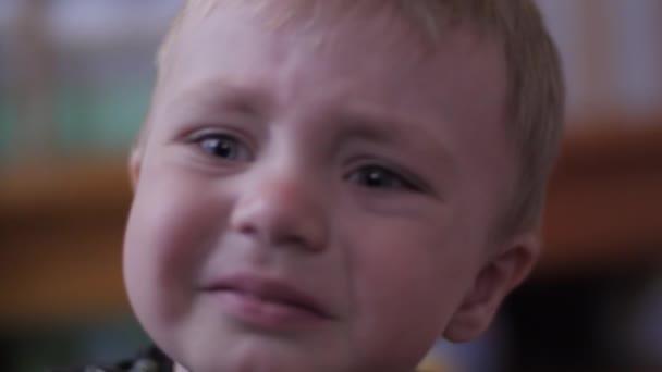Krásný roztomilý chlapeček je smutný a pláče sedí na posteli v pokoji, zpomalený film
