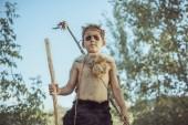 Fotografie Caveman, männliche junge mit alten Primitiven Waffe Jagd im Freien. Alter Krieger
