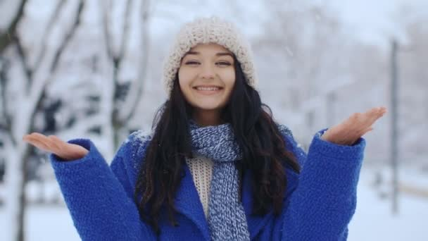 Happy smiling women having fun in the snow weather. Snow falling on the girl from tree. Snowflakes in slow motion 4k uhd footage. Christmas, New Year winter holidays concept. Gorgeous mixed race Asian