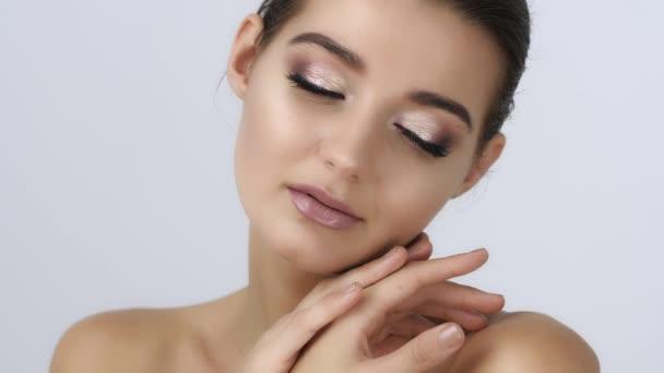 Krásná mladá žena s čisté kůže a dokonalý make-up dotknout vlastní tvář. Ošetření obličeje. Kosmetiku, pleť péče, krásy a wellness koncept. Slow motion 4k Uhd vysoce kvalitní ostré záběry.