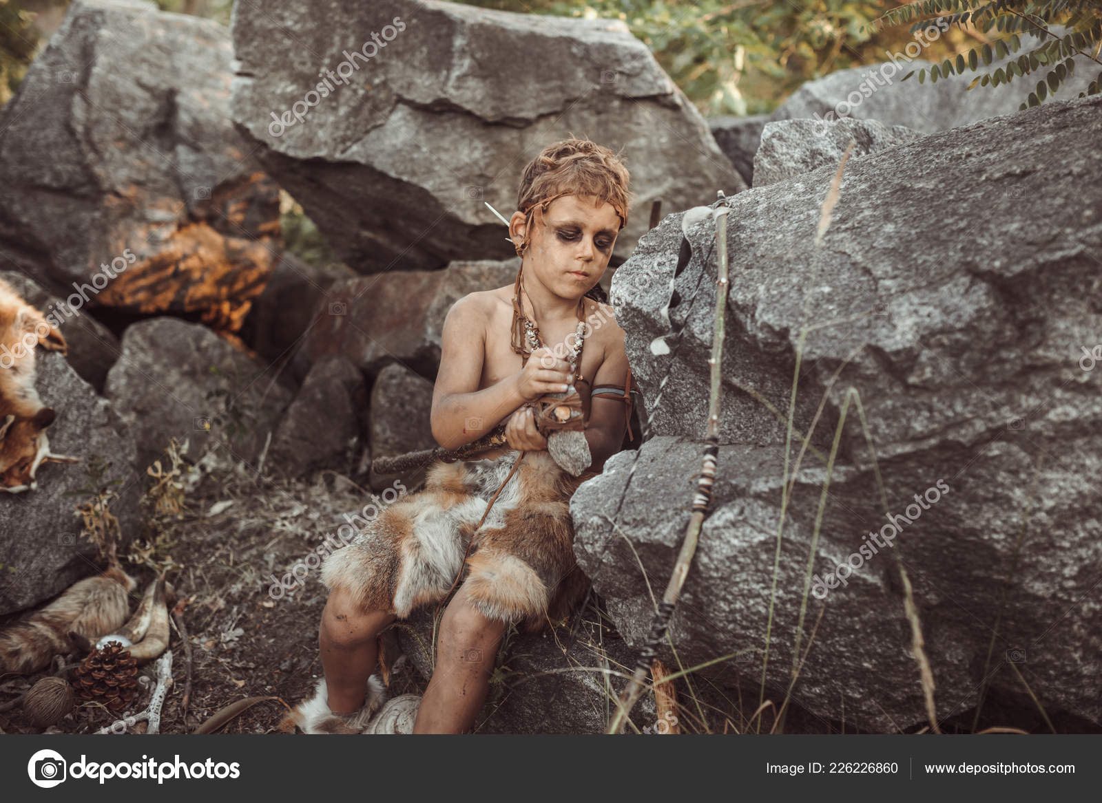 Caveman, manly boy making primitive stone weapon in camp