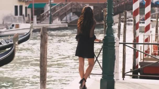 Romantic tourist woman on pier against beautiful view on venetian chanal in Venice, Italy.