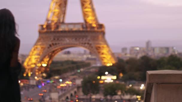 Szép, fiatal lány, figyelembe fotó neki mobil telefon az Eiffel-torony az Eiffel-torony közelében.