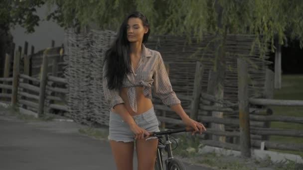 junge Frau geht mit Fahrrad im Freien