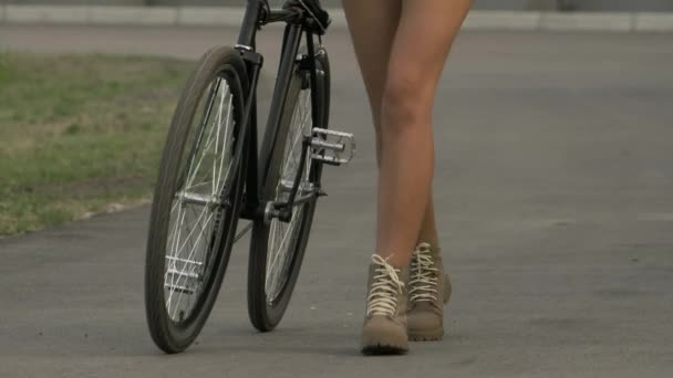 Young woman walking with a bicycle outdoor