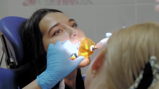 Nahaufnahme des Zahnarztes mit Zahnheillicht. Patientengesicht mit offenem Mund im Zahnarztstuhl. Professionelle Zahnsanierung in der Zahnklinik. Zeitlupe 4k uhd hochqualitatives Filmmaterial.