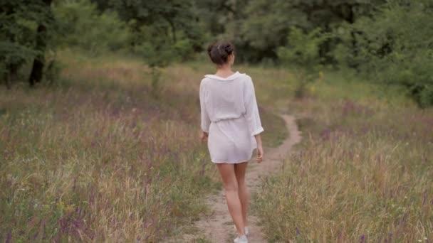 Beautiful woman walking outdoors on nature