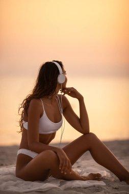 Woman in Bikini Enjoying Music with Headphones on Nature