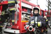 Skupina hasičů v uniformě kolem hasičský vůz se připravují na požár uhasit