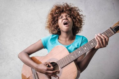 Young Afro woman singing and playing on a guitar.