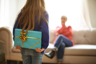 Young girl hiding a present behind her back.