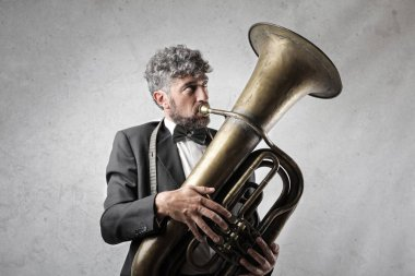 Curly-haired businessman with bow-tie playing the tuba indoor.