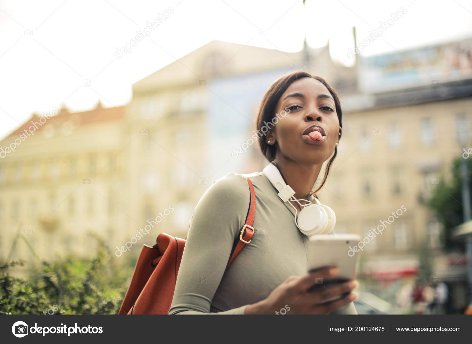 Giovane bella donna di Afro con cuffie e lo zaino che fa un fronte  divertente e che mostra la sua linguetta — Foto di olly18 48228917dd59