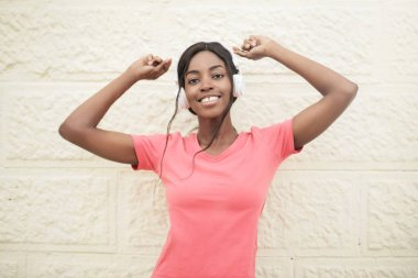 Young beautiful Afro woman with headphones stretching in front of a wall.