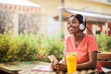 Young beautiful Afro woman with headphones and smartphone relaxing on a terrace and listening to music.
