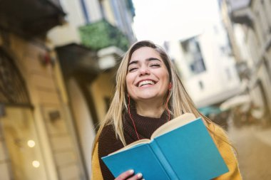 Young teenager with a book smiling and walking in the city.