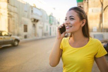 """Картина, постер, плакат, фотообои """"молодая красивая женщина в желтой футболке ходит и разговаривает по смартфону в городе . картины"""", артикул 200157972"""