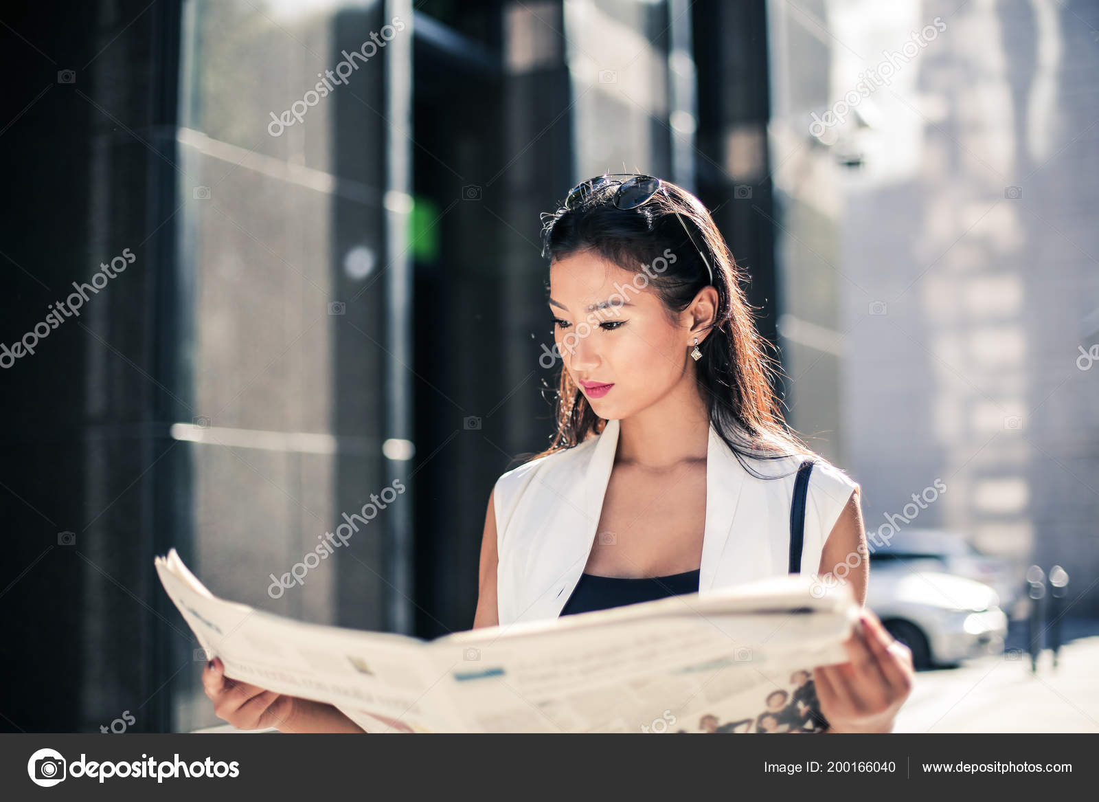 young asian woman reading newspaper street city — stock photo
