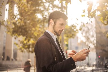 Young businessman with earphones and a coffee to go in his hand, checking his smartphone in the city.